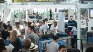 Viajeros, pasando los controles de seguridad tras hacer largas colas en El Prat
