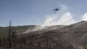 Un helicóotero sobrevuela las zonas calcinadas por las llamas