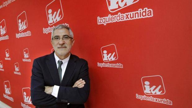Gaspar Llamazares posa frente a las siglas de IU en Asturias