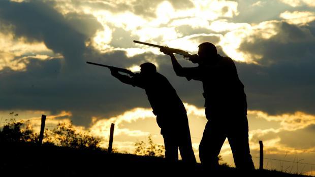 Dos varones cazando en una finca