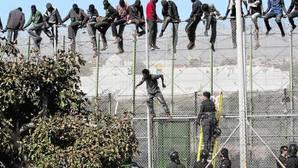 Varios inmigrantes de origen subsahariano encaramados a la valla de Melilla