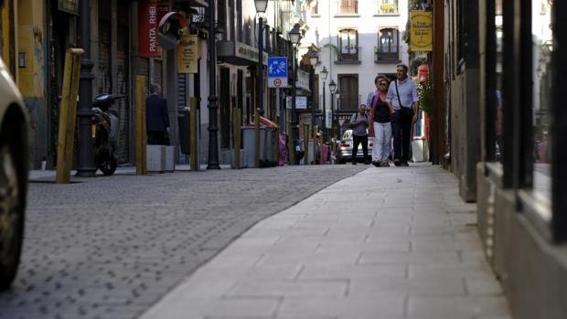 Una pareja pasea, ayer, por la calle de Hernán Cortés, en el barrio de Chueca, tras las obras