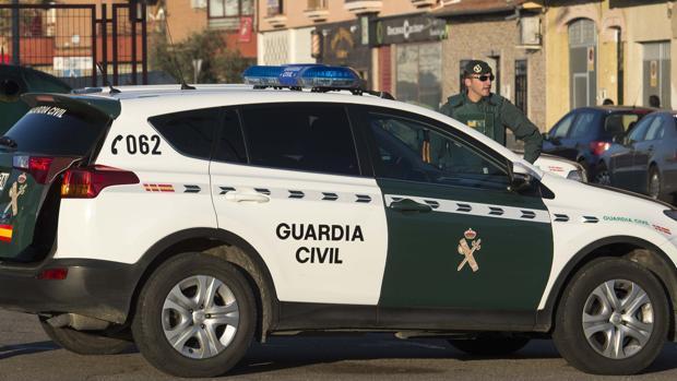 Imagen de archivo de un agente y un coche de la Guardia Civil