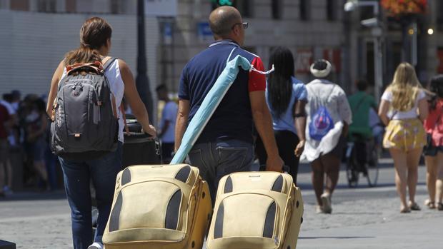 Dos turistas pasean por la capital con sus maletas