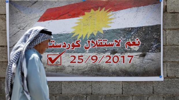 Un hombre pasa junto a un cartel a favor del referéndum, en Kirkuk, Irak