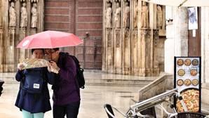Unos turistas se protegen de la lluvia en una imagen de archivo captada en el centro de Valencia
