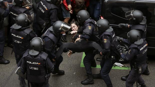 Agentes de la Policía Nacional trasladan a una joven frente al colegio Ramón Llull de Barcelona.