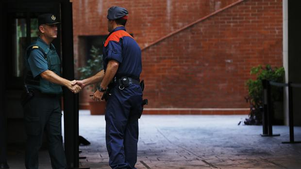 Un mosso d'esquadra saluda a un guardia civil en la entrada de la caserna de Travessera de Gracia, en Barcelona, donde permanecían arrestadas varias de las catorce personas que fueron detenidas por delitos de malversación, prevaricación y desobediencia