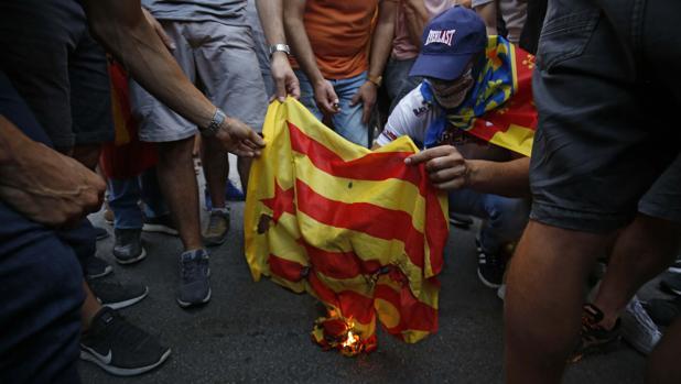 Un grupo de personas quema una estelada independentista, este lunes en Valencia