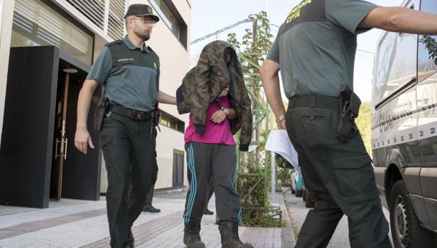 El brigadista detenido es trasladado a un furgón de la Guardia Civil para su ingreso en prisión