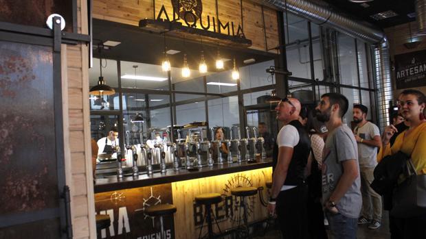 Barra y grifos, con la cocina detrás, de Alquimia Beer Company