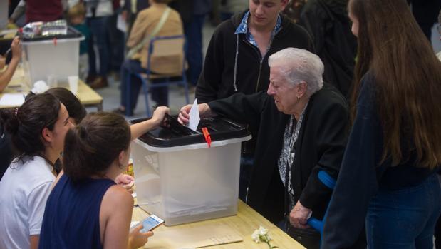 Una señora mete su voto en una urna durante el referéndum ilegal del 1-O