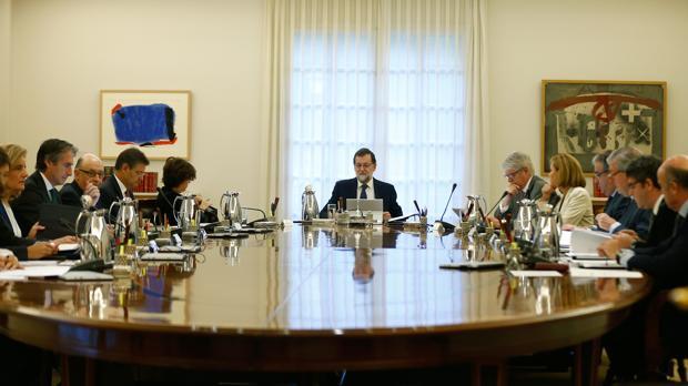 El presidente del Gobierno, Mariano Rajoy (c), junto a los ministros en La Moncloa