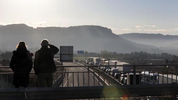 Dos personas observan las retenciones de ayer en la A-2