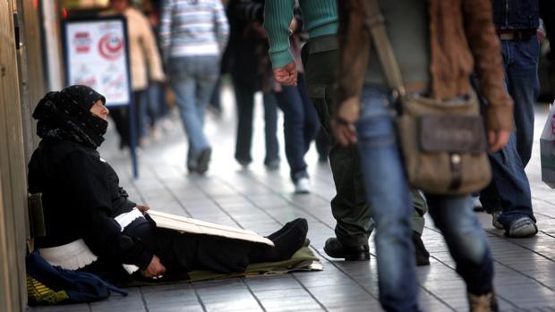 Una mujer pide limosna en una calle del centro de Valencia