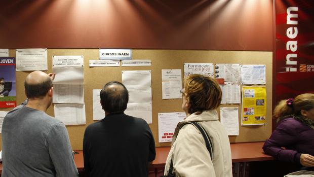 Desempleados revisando el tablón de anuncios en una oficina del Inaem