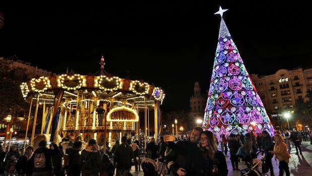 La plaza del Ayuntamiento de Valencia, iluminada con luces de Navidad y con la pista de hielo
