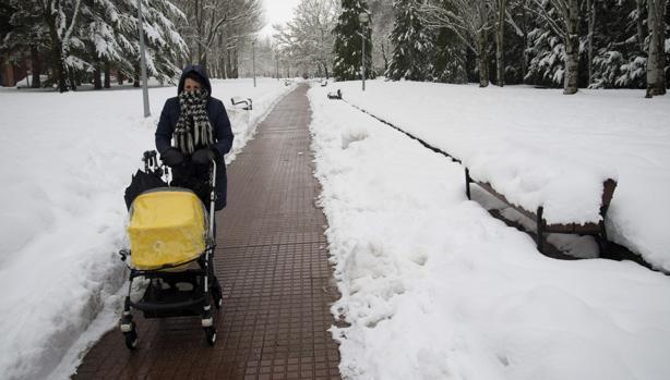 Un mujer pasea con un bebé por uno de los parques nevados de la ciudad de Vitoria