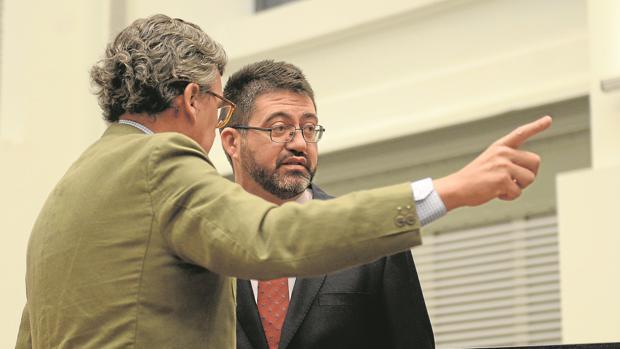 El secretario del Pleno indica ayer a Sánchez Mato cuál es su nuevo asiento en el hemiciclo