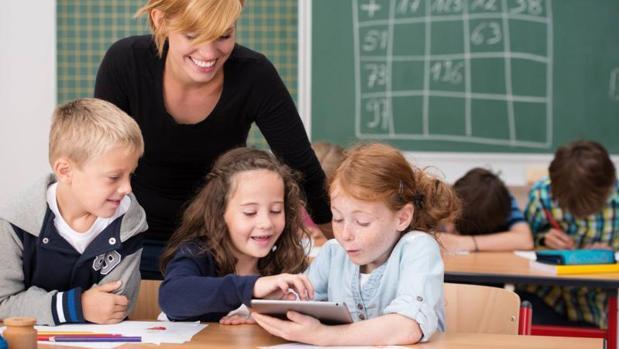 Niños juegan con un dispositivo conectado a Internet en un colegio