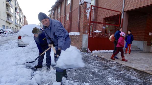Dos operarios tratan de quitar la nieve a las puertas de un colegio, en la capital abulense
