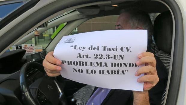 Un taxista muestra un cartel de protesta contra la norma del Consell