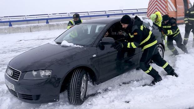 Un equipo de rescate de la UME, junto a un guardia civil, tratan de rescatar un coche atrapado en la nieve