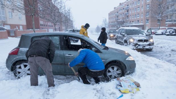 Vecinos abulenses intentan quitar la nieve caída alrededor de su coche