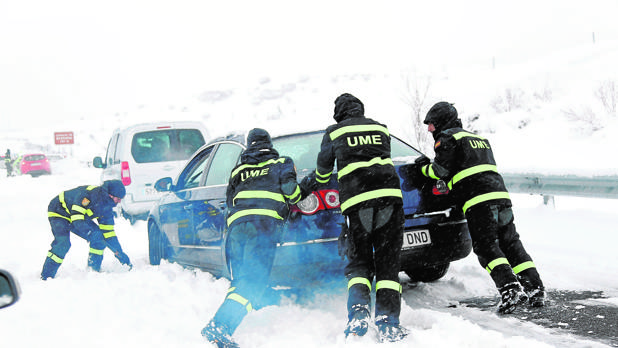 Efectivos de la UME ayudan a un vehículo a salir tras verse atrapado por la nevada en la AP-6