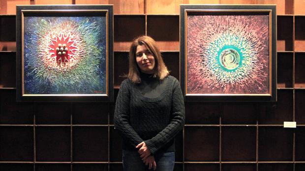Raja Azaroual y dos de sus cuadros colgados en la exposición