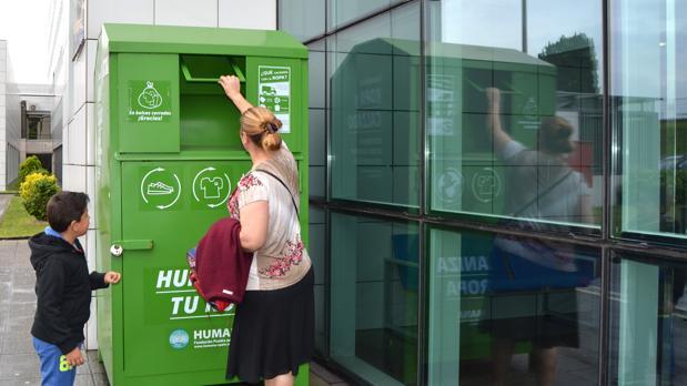 Una mujer deposita algunas prendas en un contenedor