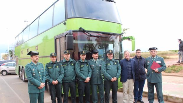 Mandos y autoridades posan ante el autobús en el que viajaban los detenidos
