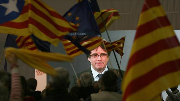 Rostro del prófugo Puigdemont proyectado en una pantalla ante espectadores con banderas independentistas