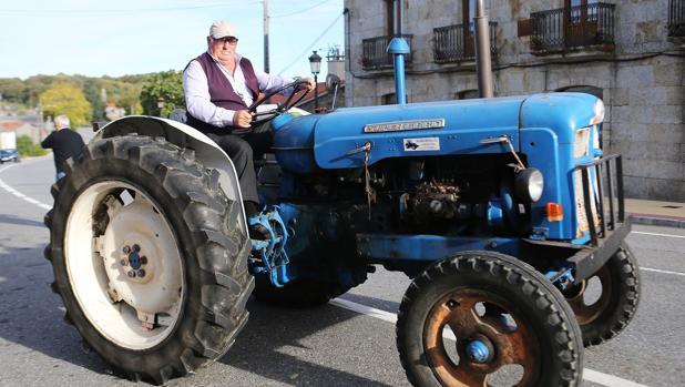 Un vecino de Dozón (Pontevedra) circula con su tractor por las calles del pueblo