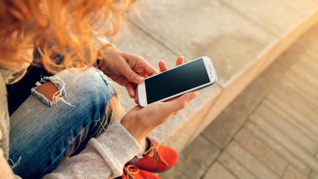 Una joven mira su teléfono móvil