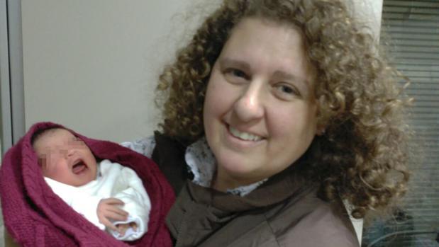 Julia Sánchez abriga a la pequeña con su chaqueta después de recogerla de la puerta de la iglesia