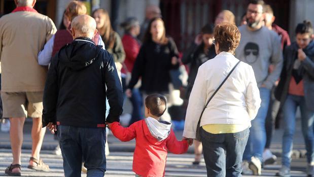 Una pareja mayor paseando a su nieto de la mano