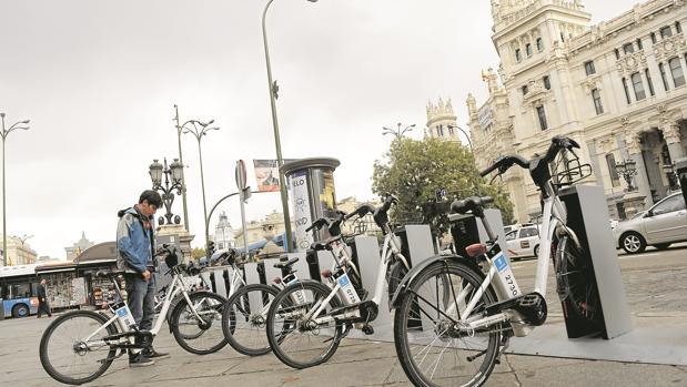 Un joven coge una bicicleta de Bicimad, en la estación situada frente al Ayuntamiento