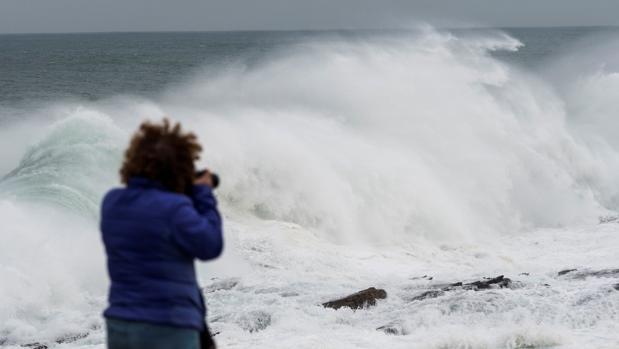 Una mujer fotografiando las olas en Ribadeo