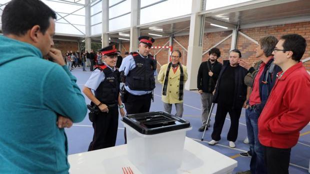 Dos mossos frente a una mesa de votación en un colegio electoral del referéndum ilegal del 1-O