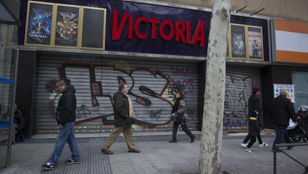 Varios transeúntes pasan delante de los clausurados cines Victoria, ayer por la tarde