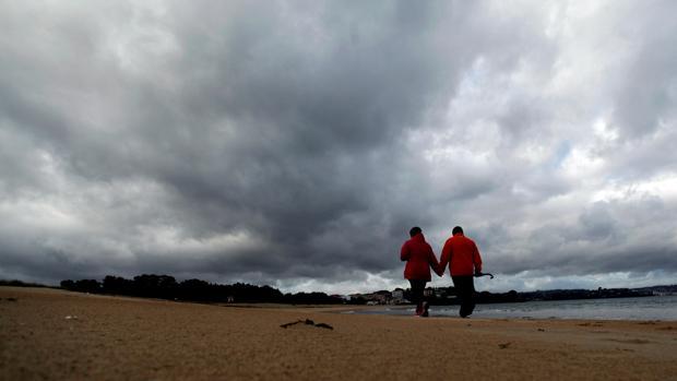 Una pareja caminando este viernes en la playa de Miño antes de la llegada de Félix