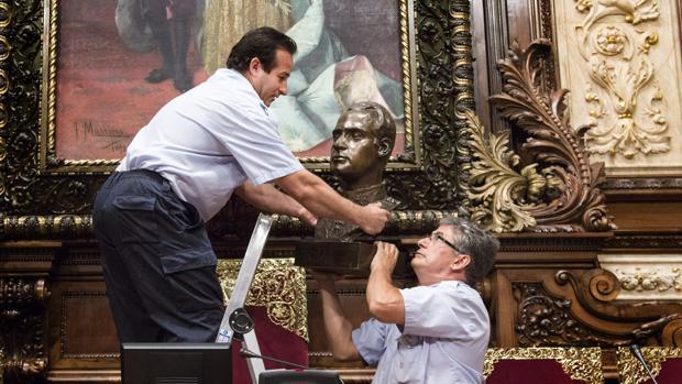 Dos operarios retiran el busto del Rey Juan Carlos del Salón de Plenos del Ayuntamiento