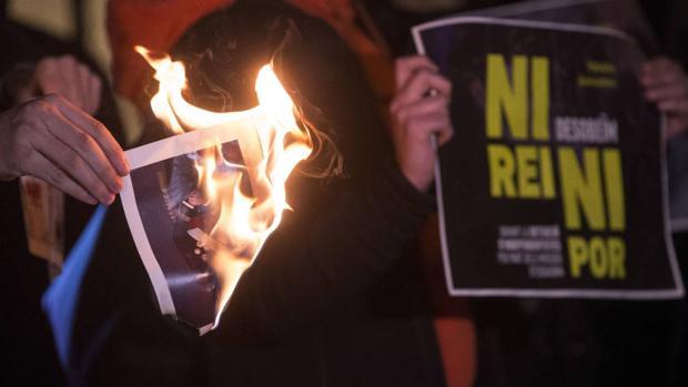 Manifestantes quemando fotos del Rey