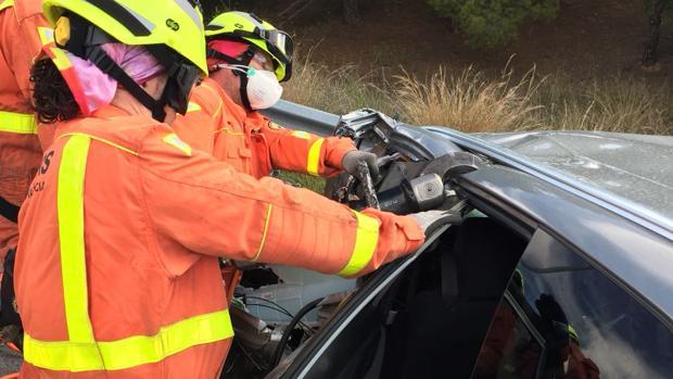 Efectivos de Bomberos excarcelando a una persona del coche implicado en el accidente