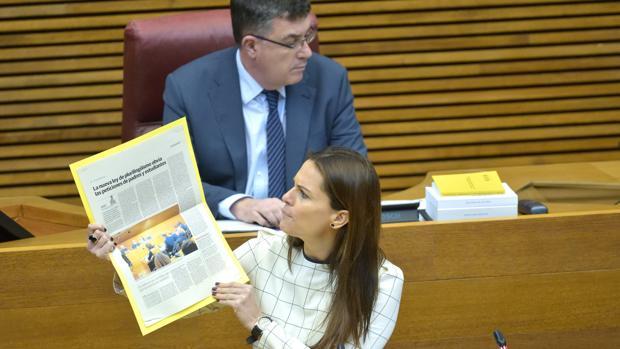Beatriz Gascó muestra un recorte de prensa en las Cortes Valencianas, ante el presidente de la Cámara, Enric Morera