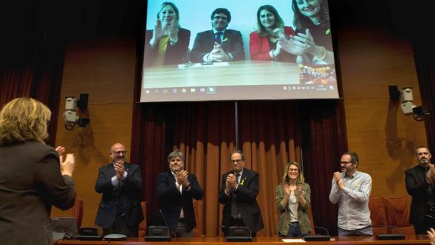 Los diputados de JpC, con Torra en el centro, con Puigdemont en pantalla desde Berlín