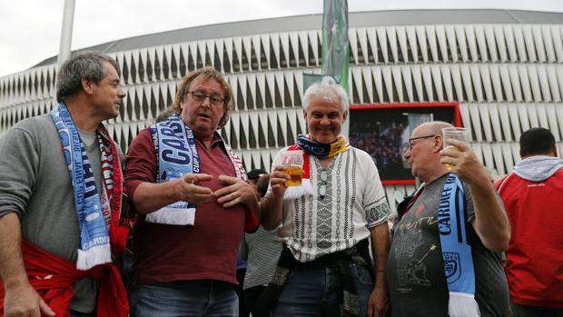 Aficionados del Cardiff Blues galés (i) junto a un aficionado del Gloucester Rugby inglés