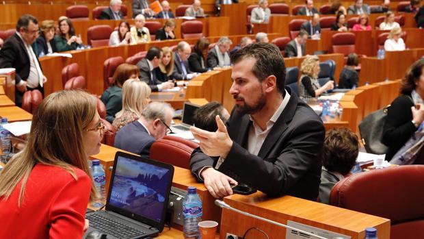 El portavoz del Grupo Socialista, Luis Tudanca. conversa con su compañera Ana Muñoz, durante el Pleno