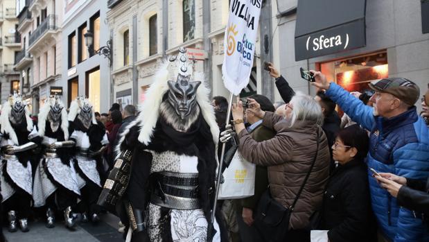 Espectadores del desfile en las calles de Madrid fotografían las fiestas alicantinas